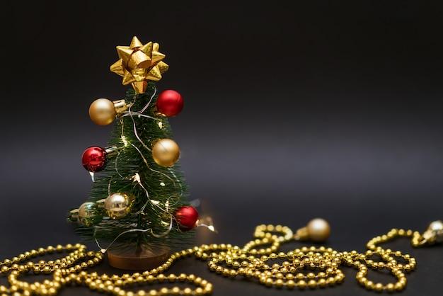 Dekorativer kleiner weihnachtsbaum auf schwarzem hintergrund mit einer goldenen kette kleine kugeln hängen am baum...