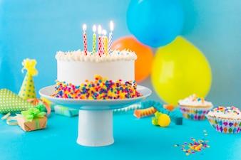 Dekorativer Kuchen mit beleuchteter Kerze auf Kuchenständer