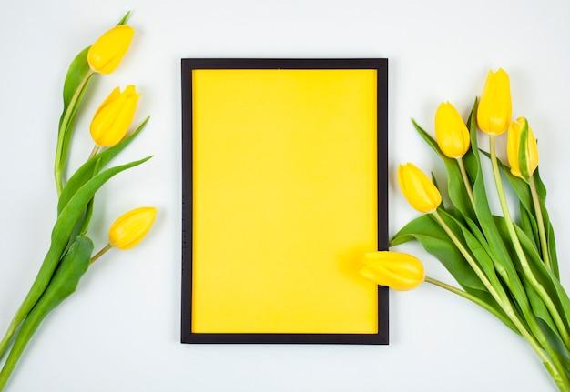 Dekorativer leerer rahmen mit kopienraum und blumenstrauß von tulpen