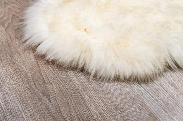Dekorativer pelzteppich auf holzbodenhintergrund. weiße tierhaut auf dem parkettboden in der wohnung. matte aus natürlicher kaninchenhaut.