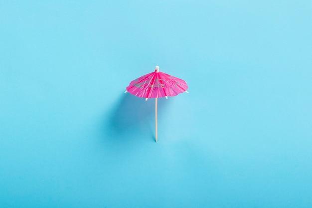 Dekorativer regenschirm für einen cocktail auf blauem hintergrund. flache lage, draufsicht