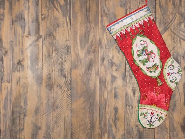 Dekorativer roter stiefel, der am hölzernen hintergrund hängt. weihnachtsdekorationen
