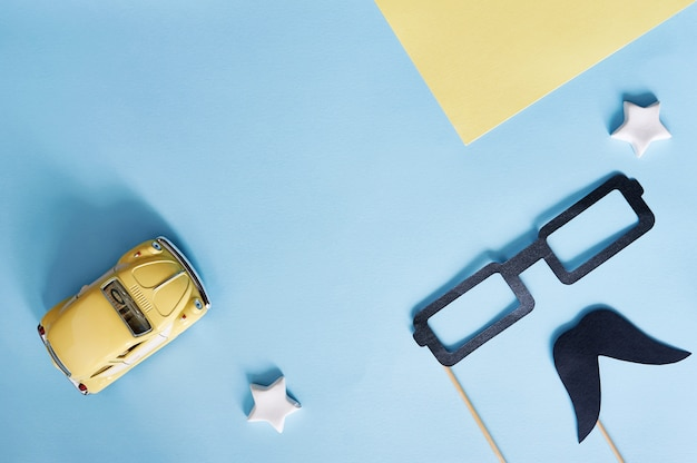 Dekorativer schwarzer papierschnurrbart, gläser und gelbes spielzeugauto auf einem blauen hintergrund mit platz für text