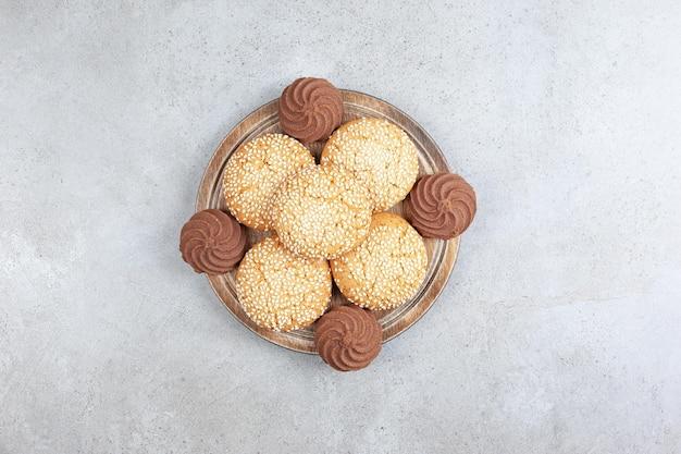 Dekorativer stapel von hausgemachten keksen auf holztablett, auf marmorhintergrund. hochwertiges foto
