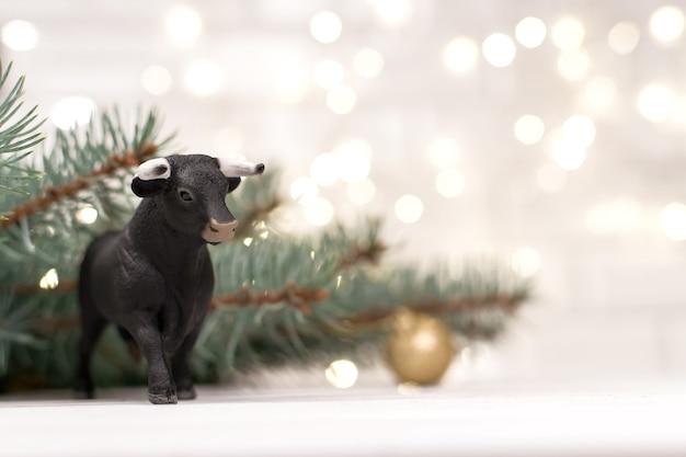 Dekorativer stier, symbol des neuen jahres auf dem hintergrund von weihnachtsbäumen und blauem bokeh.