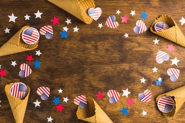 Dekorativer waffelkegel mit ausweis und sternen der amerikanischen flaggen für den 4. juli auf hölzernem schreibtisch