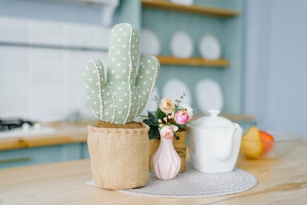 Dekorativer weicher kaktus in einem topf. rosa vase mit blumen und einem weißen kessel im dekor der küche im skandinavischen stil, minimalismus prägnant