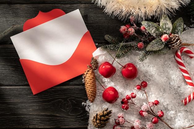 Dekorativer weihnachtshintergrund mit einem roten weihnachtsumschlag und einem leeren weißen blatt