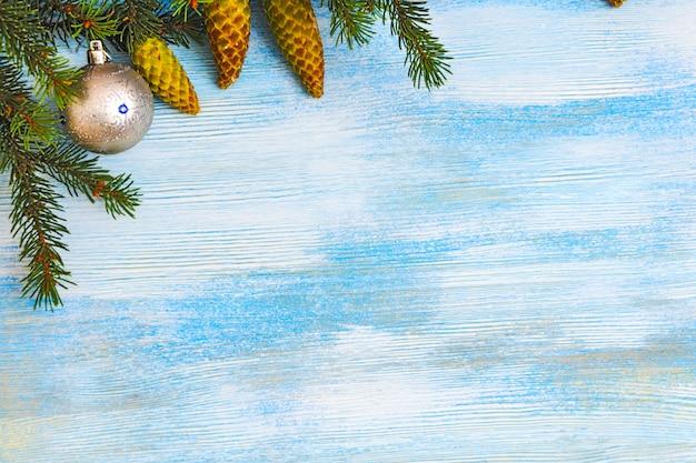 Dekorativer weihnachtshintergrund. pelzbaumzweig mit zapfen und weihnachtskugeln auf einem blauen hölzernen hintergrund.