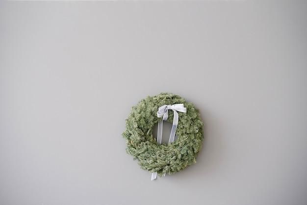 Dekorativer weihnachtskranz mit einer grauen schleife auf dem hintergrund einer grauen betonwand mit einem kopienraum