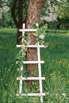Dekorativer weißer stehleiter in einem blühenden garten im frühjahr. romantisches dekor