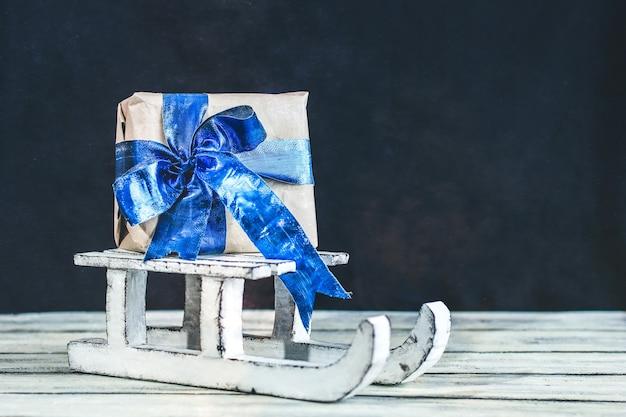Dekorativer winterschlitten. weißer schlitten. ein geschenk auf einem schlitten.