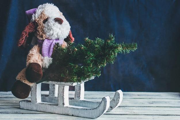 Dekorativer winterschlitten. weißer schlitten. ein stofftier und ein weihnachtsbaum auf einem schlitten