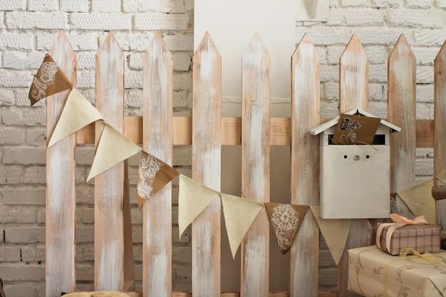 Dekorativer zaun mit einer girlande aus fahnen und einem briefkasten