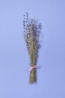 Dekorativer zweig aus trockenen natürlichen lavendelblüten in derselben farbe mit weichen schatten, platz für text. flach liegen.