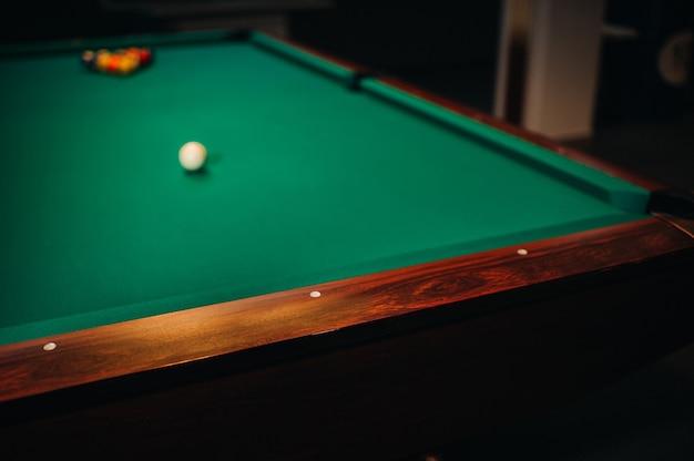 Dekoratives billardloch und grüner tisch mit bällen im billardclub.