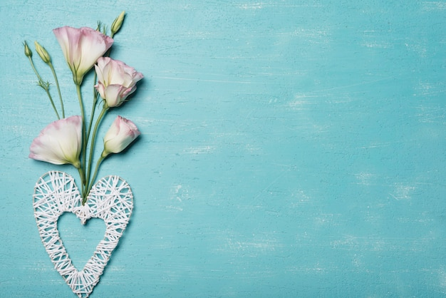 Dekoratives handgemachtes herz mit eustoma blüht gegen blauen strukturierten hintergrund