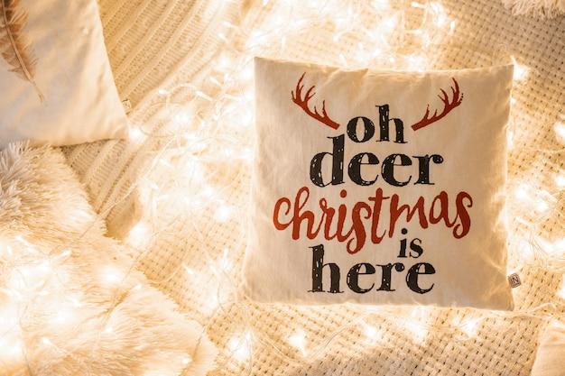 Dekoratives kissen mit einer aufschrift in den lichtern. konzept für weihnachten, neujahr