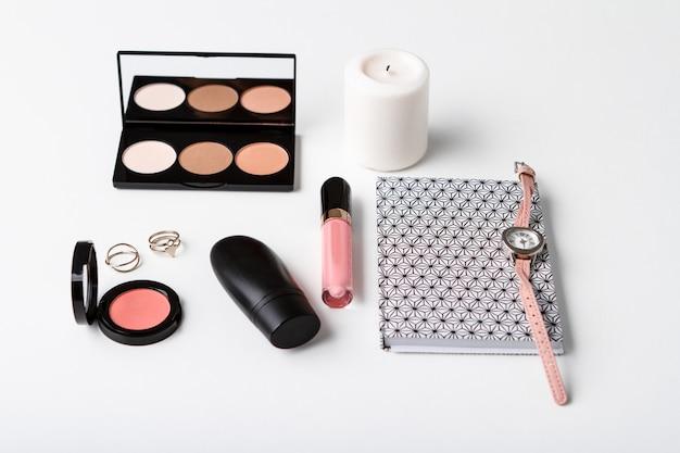 Dekoratives kosmetikarmbanduhr-notizbuch und kerze über weißer oberfläche