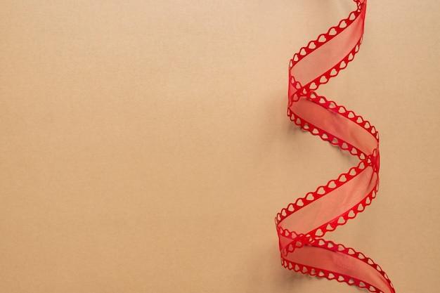 Dekoratives rotes band mit herzen, spiralförmig auf beigem hintergrund gedreht. fetstive-konzept mit kopierraum.