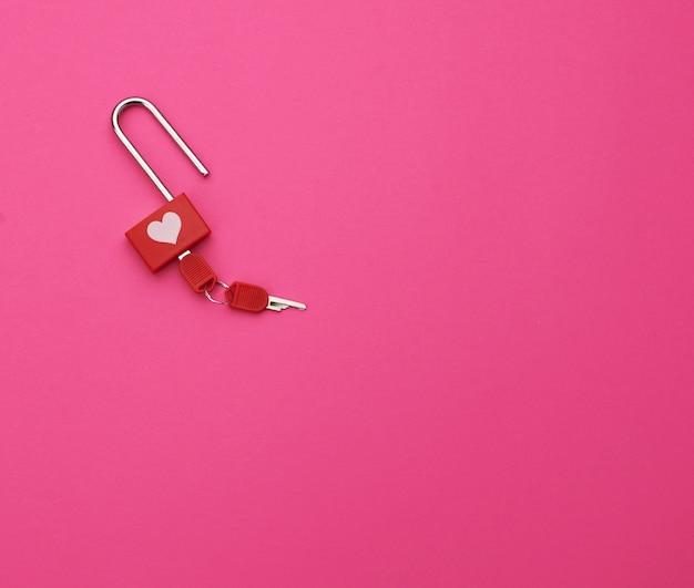 Dekoratives rotes metallschloss und ein satz schlüssel auf einem rosa hintergrund