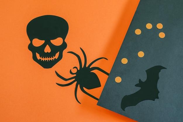 Dekoratives schwarzes schädelspinnenfledermaus-tier und erbsen auf dem papier-halloween-hintergrund nettes design für grußkarte oder partyeinladung