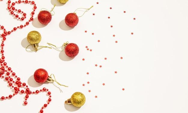 Dekoratives weihnachtsspielzeug in roter und goldener farbe mit roten perlen für dekor und sterne auf weißem hintergrund. platz für kopierraum, flach liegen. urlaubskonzept. sicht von oben