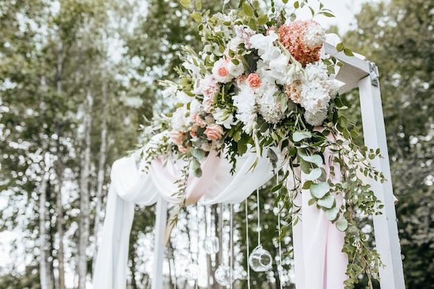 Dekorieren des bogens mit blumen und stoff für eine hochzeitszeremonie in der natur