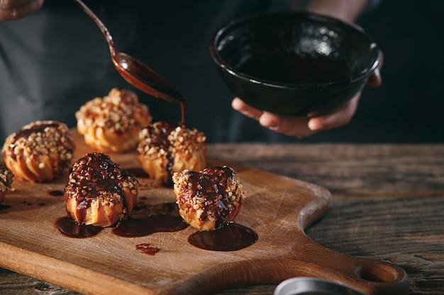 Dekorieren sie köstliche hausgemachte eclairs mit schokolade und erdnüssen
