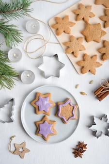 Dekorieren von lebkuchenplätzchen mit violettem zuckerguss auf weißem holztisch mit schneidern und kerzen