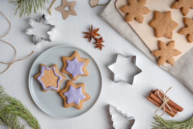 Dekorieren von lebkuchenplätzchen mit violettem zuckerguss, serviert auf grauem teller auf holztisch mit textil