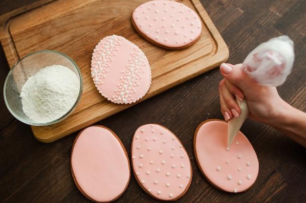 Dekorieren von rosa hochzeitskeksen der hochzeit mit weißem zuckerguss auf rustikaler holztisch-draufsicht