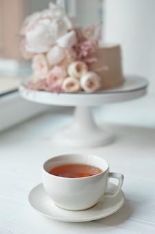 Dekoriert mit frischen blumen, einem weißen nacktkuchen, einem stilvollen kuchen für hochzeiten und veranstaltungen eine weiße tasse mit einem heißen getränk