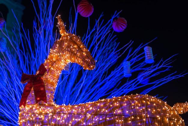 Dekorierte rentierinstallation, die zu weihnachten mit lichtern beleuchtet wird