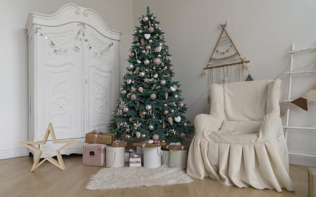 Dekorierter raum für weihnachtsfeiertage - geschenke unter weihnachtsbaum und weißer garderobe und bedecktem lehnsessel