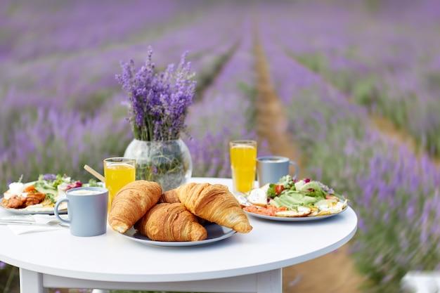 Dekorierter tisch mit essen im lavendelfeld
