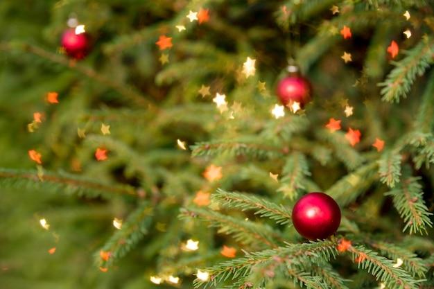 Dekorierter weihnachtsbaum auf unscharfem, funkelndem und feenhaftem hintergrund. magisch dekorierter weihnachtsbaum mit roten kugeln auf einem verschwommenen glänzenden, funkelnden hintergrund.