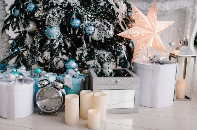 Dekoriertes weihnachtsinterieur. baum mit geschenkboxen in einem weißen raum. tannenbaum mit girlanden verziert.