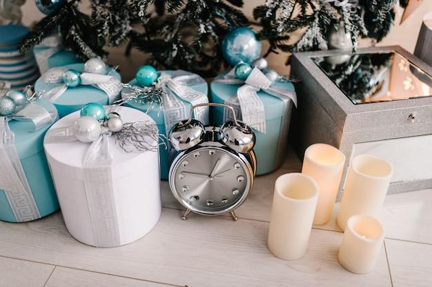 Dekoriertes weihnachtsinterieur. baum mit geschenkboxen, uhr, kerzen in einem weißen raum. dekor. fröhliche weihnachten. das konzept der winterferien.
