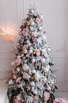 Dekoriertes weihnachtsinterieur. mit tannen geschmückte girlanden mit geschenkboxen in einem weißen raum.