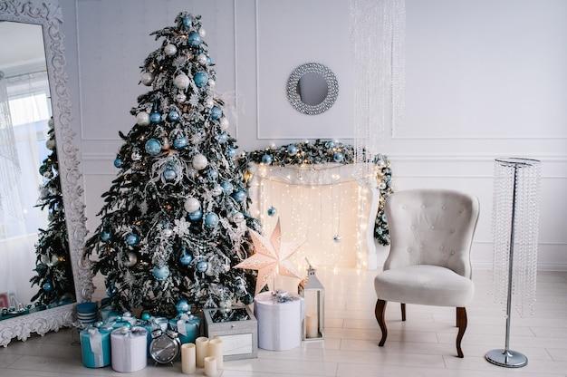 Dekoriertes weihnachtsinterieur. weihnachtsbaum mit geschenkboxen in einem weißen raum. tannenbaum, sessel, kamin mit girlanden verziert.