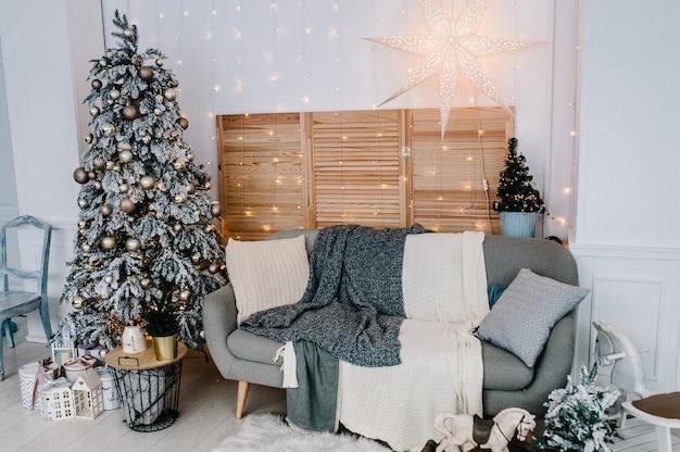 Dekoriertes weihnachtsinterieur. weihnachtsbaum mit geschenkboxen in einem weißen raum.