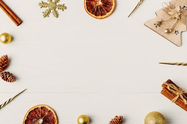 Dekorrahmen, weihnachtsattribute auf einem weißen holztisch. platz für text, leer für postkarte. copyspace.
