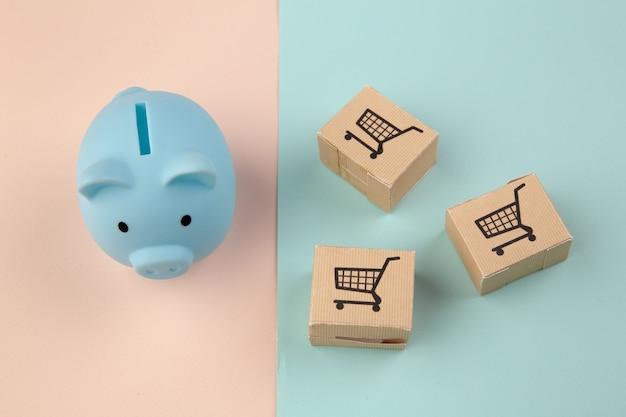 Delievery boxen und blaues sparschwein auf buntem backplatz. online-shopping- und lieferservice-konzept.