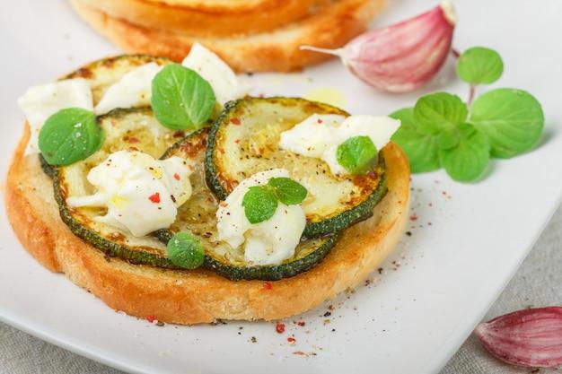 Delikatesse bruschetta mit gebratener oder gebackener zucchini, mozzarella, knoblauch, minze und gewürzen. mediterranes sandwich.