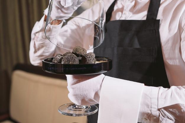 Delikatesse des restaurantkochs. trüffel veganes essen pilz. kellner-service-mahlzeit-konzept