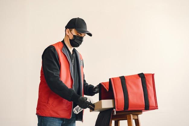 Delivery man spray desinfektion auf eine box