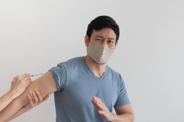 Dem asiatischen mann wird ein impfstoff zum schutz vor viren injiziert