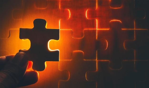 Dem hölzernen puzzle fehlen teile, die zum anzünden bereit sind. es ist ein geschäftskonzept für den erfolg von komponenten.