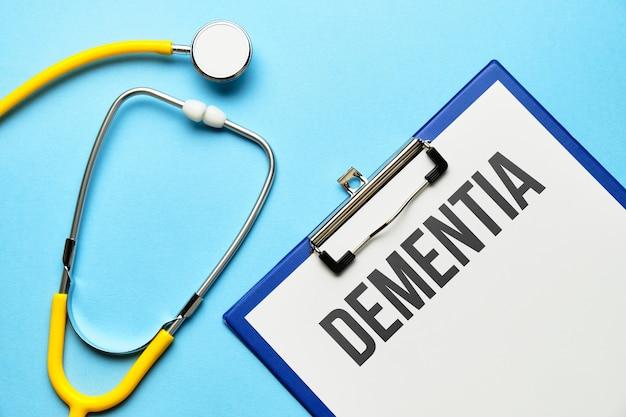 Demenzdiagnosekonzept auf medizinischer tablette mit dokumenten mit stethoskop.